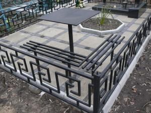 кованая ограда, скамейка и столик на кладбище