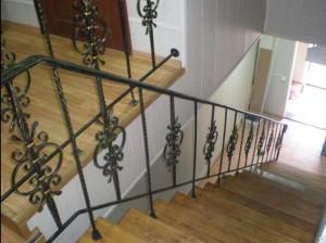 ковано-сварные перила для узкой деревянной лестницы