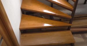 металлическая лестница на второй этаж с коваными перилами и деревянной обшивкой